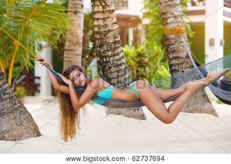 Young Lady With Long Blonde Hair Relaxing In Hammock On The Tropical Beach