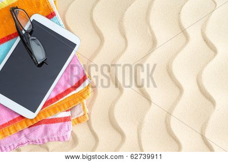 Tablet And Glasses On A Colorful Beach Towel