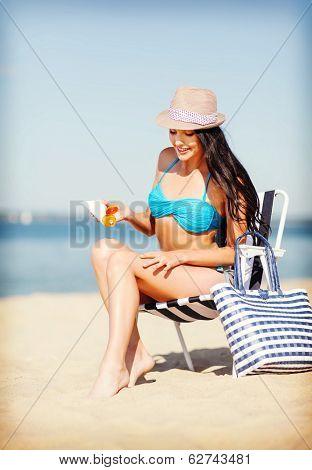 summer holidays and vacation - girl applying sun protection cream