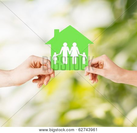 real estate and family home concept - isolated picture of male and female hands holding green paper house with family