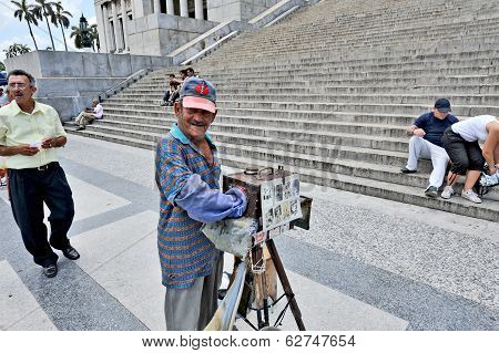 A man with an old box camera in front of El Capitolio