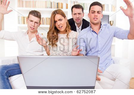Hocked Casual Group Of Friends Sitting On Couch Looking At Laptop