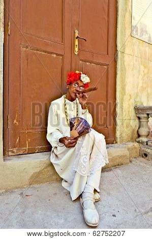 An old woman sitting with a huge cigar