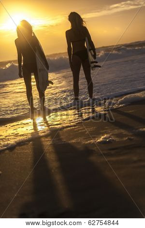 Beautiful young women surfer girls in bikinis with surfboards on a beach at sunset or sunrise