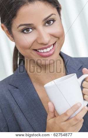 Beautiful young Latina Hispanic woman businesswoman with perfect teeth, smiling & relaxing in her office drinking a cup of coffee or tea