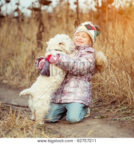little cute girl with her dog  walking in a field in autumn