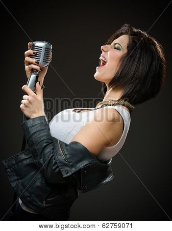 Side view of female rock musician wearing black jacket and keeping microphone on grey background. Concept of music and rave