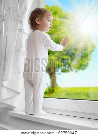 Little boy looking at rural garden from a window. Environmentally friendly living concept.