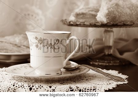 Elegant still life of beautiful vintage teacup and saucer with sweet pastries on pedestal plate in background. Closeup in sepia tones with shallow dof.
