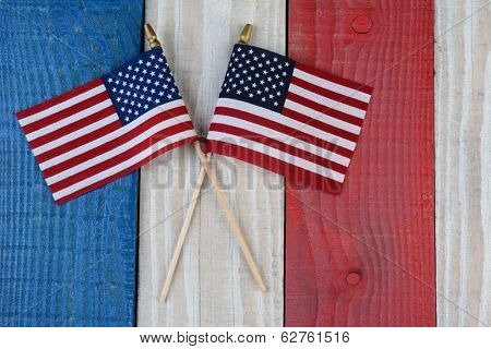 Two American Flags on a red, white and blue painted wood surface. Perfect for Fourth of July or Memorial Day projects.