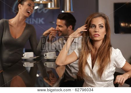 Unhappy young woman sitting in bar, boyfriend flirting with waitress at background.