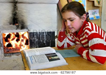 Russian Schoolgirl Reads Textbook Sitting Beside An Open Fire Wood Stove.
