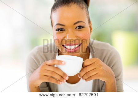 happy african woman drinking coffee in the morning at home