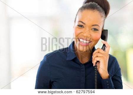 attractive african businesswoman using landline phone
