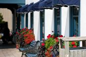 stock photo of awning  - The front of a restaurant with blue awnings over each window flower boxes brimming with colorful flowers - JPG
