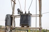 picture of transformer  - small transformer fixed to a double pole structure on a light blue sky background - JPG