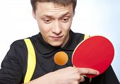 foto of ping pong  - Young man playing ping pong against a blue background - JPG