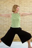 stock photo of virabhadrasana  - Senior woman laughing as she engages in the strength building warrior pose - JPG