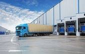 stock photo of warehouse  - Unloading cargo truck at a warehouse building - JPG
