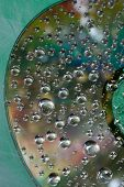 pic of refraction  - A close-up of water drops refracting light on the surface of a compact disc.