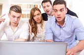 foto of pissed off  - shocked and frustrated casual group of friends sitting on couch looking at laptop pissed off friends because results cheering on computer - JPG