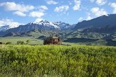 pic of covered wagon  - An old covered wagon sits in front of the Absaroka Mountains of Wyoming - JPG