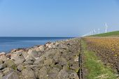 stock photo of dike  - Dutch dike along the sea with wind turbines - JPG