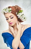 Portrait of beautiful girl in studio with spring flowers in her hair. Sexy young woman in blue