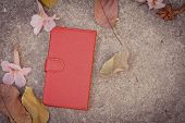 pic of floor covering  - Smartphone leather case cover with dried leafs and flower on the floor - JPG