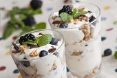 foto of yogurt  - Layered berries yogurt and cereals in a glass - JPG