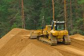 stock photo of dozer  - Yellow excavator at work in winter forest - JPG