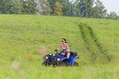 stock photo of four-wheel drive  - Elegant woman riding extreme quadrocycle in summer fields - JPG