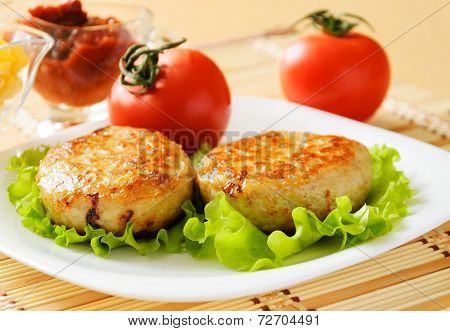 Two chicken cutlets on the green leaf lettuce.