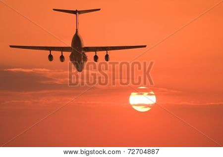 Flight of the cargo plane on the sunset background.