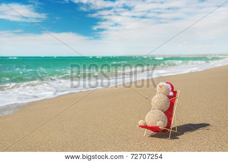 Sandy Snowman In Santa Hat Sunbathing In Beach Lounge.