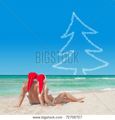 Lovers Couple In Santa Hats At Beach Against Blue Sky And Christnas Fir Tree
