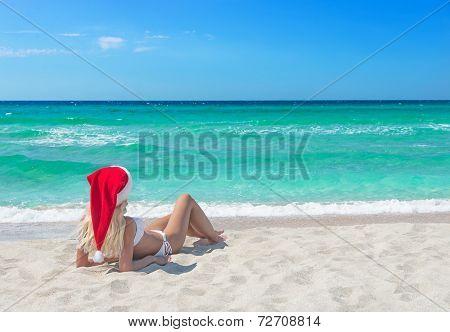 Beautiful Blonde Woman In Bikini And Red Christmas Hat On Sea Beach