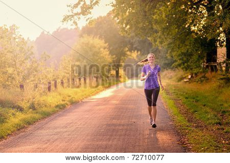 Sporty Woman Running On A Country Road