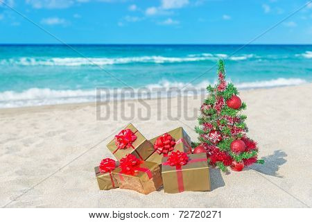 Christmas Tree And Golden Gift With Big Red Bow On The Sea Beach