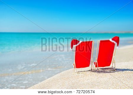 Christmas Santa Hat On Chaise Longues At White Sand Beach Against The Sea And Sky