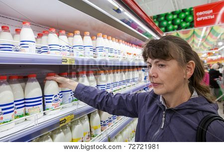 Samara, Russia - September 27, 2014: Young Woman Choosing Fresh Milk Produces At Shopping In Dairy S