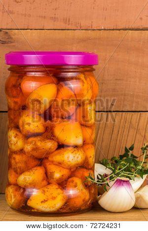 Pickled Garlic In A Jar Of Green Marjoram