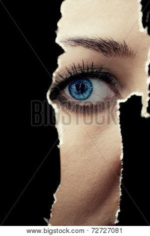 Young Woman Spying Through A Hole In The Wall