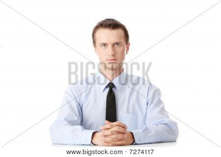 Young Businessman Sitting Behind The Desk