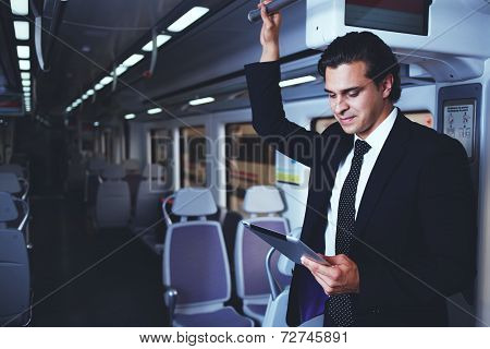 Handsome businessman working with tablet on the way to work