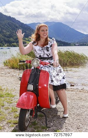 Young curvy woman sitting on a scooter with a petticoat dress and waving