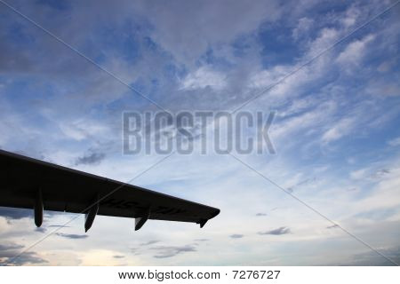 Airplane Wing On A Deep Cloudy Sky Background