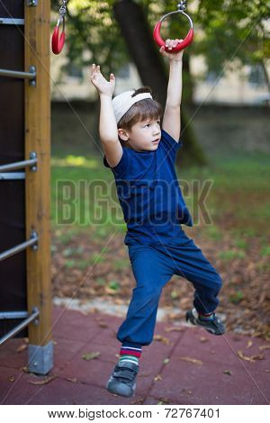 Little Brave Boy Hanging On Jungle Gym