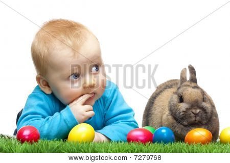 Cute Young Child With Easter Bunny And Easter Eggs In Meadow
