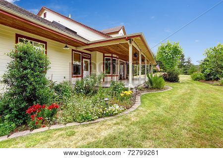 Farm House Exterior. Entrance Porch With Beautiful Flower Bed